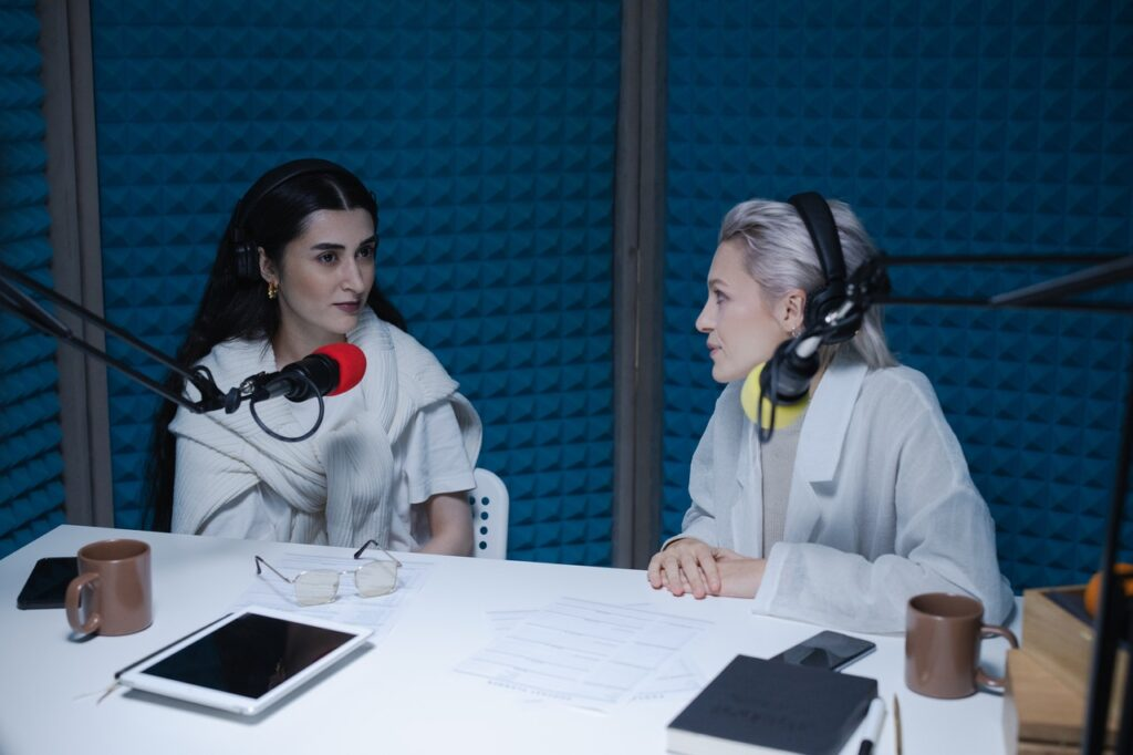 Two women face to face with microphones talking
