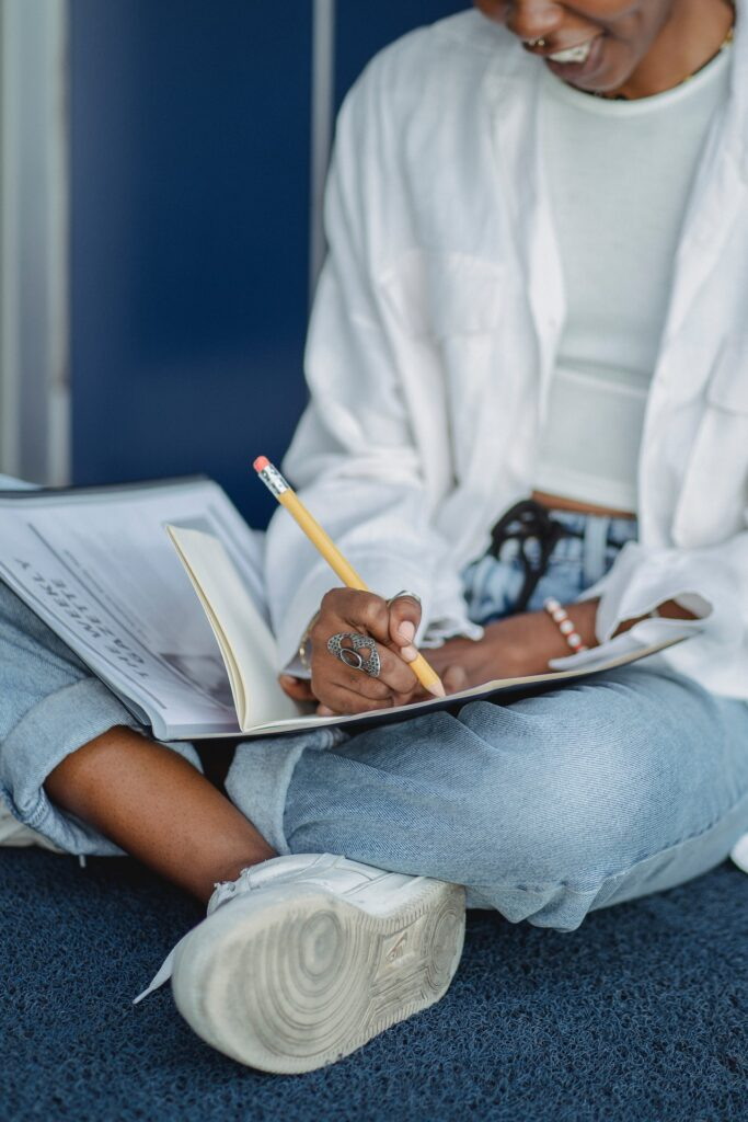 Woman sitting crosslegged writing into notebook