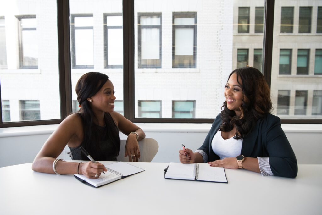 Two women talking happily to each other sitting at a desk