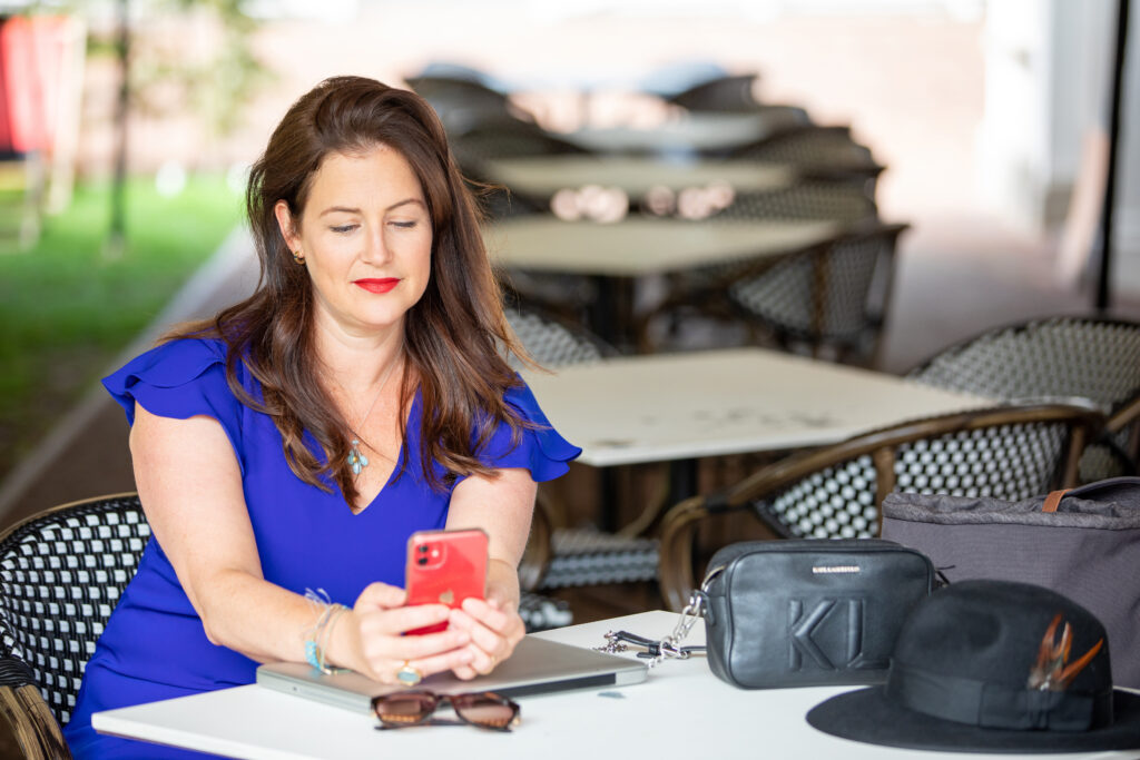 Claire Winter sitting at table looking at phone smiling