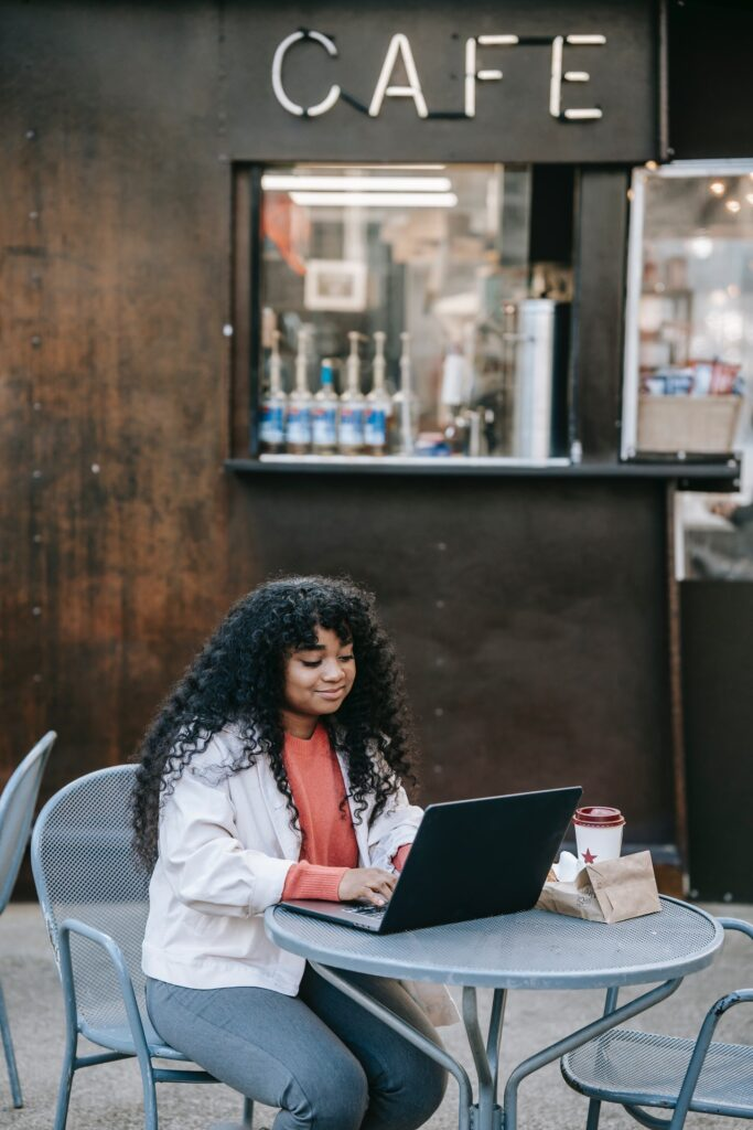 Woman sitting outside cafe typing on laptop