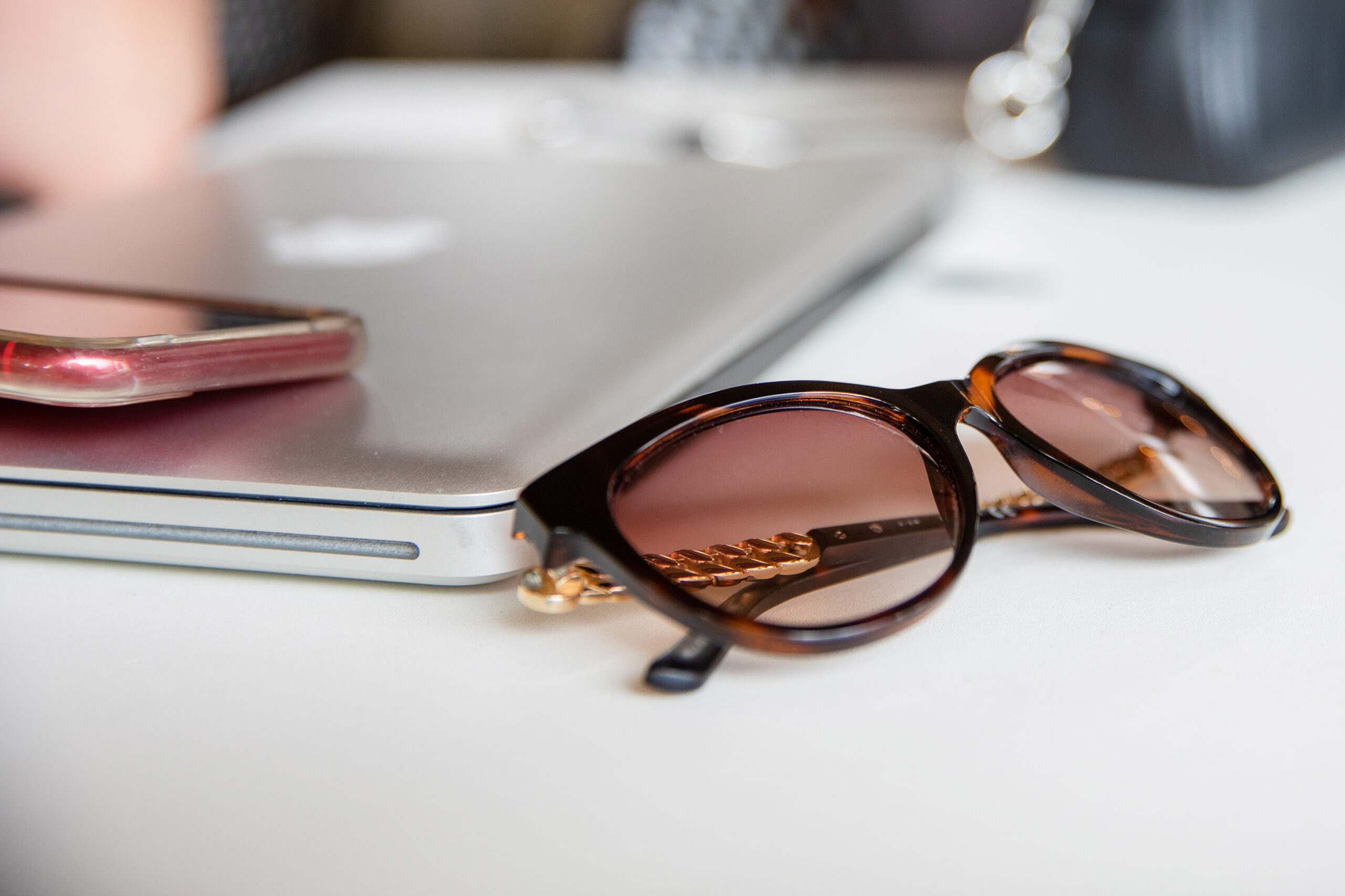 Close up of sunglasses and closed laptop
