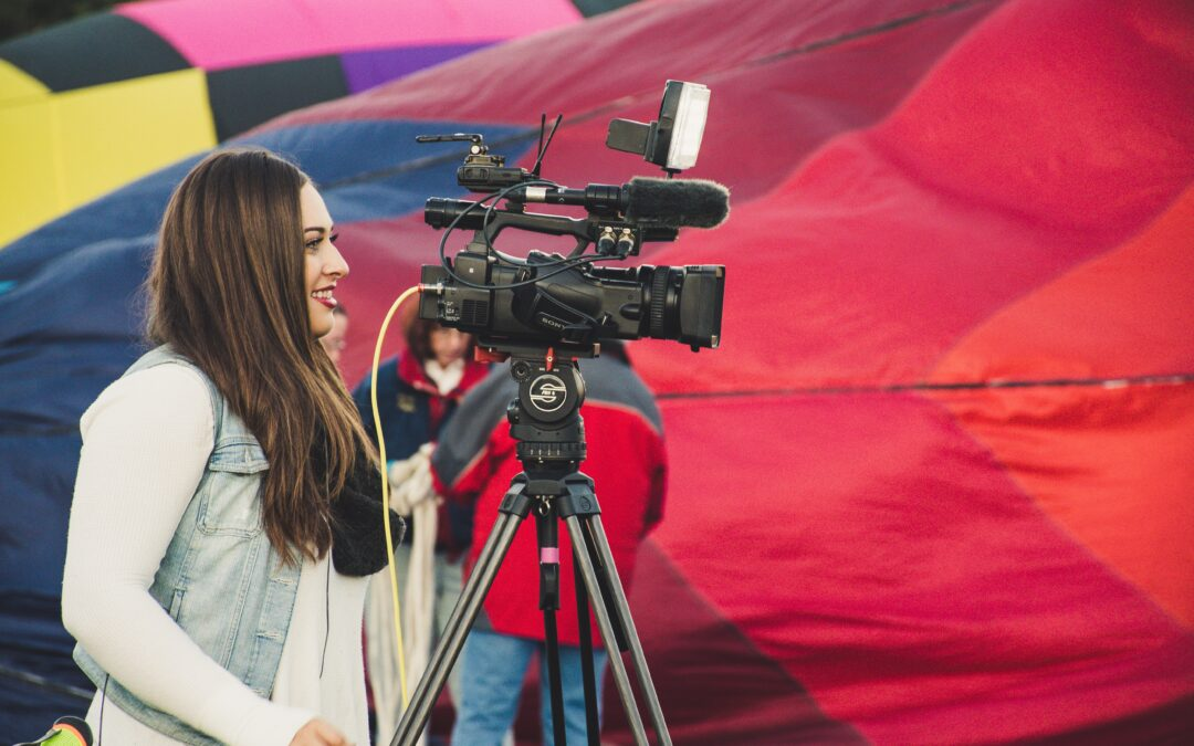 Woman standing behind a video camera set on a tripod in front of a colourful backdrop
