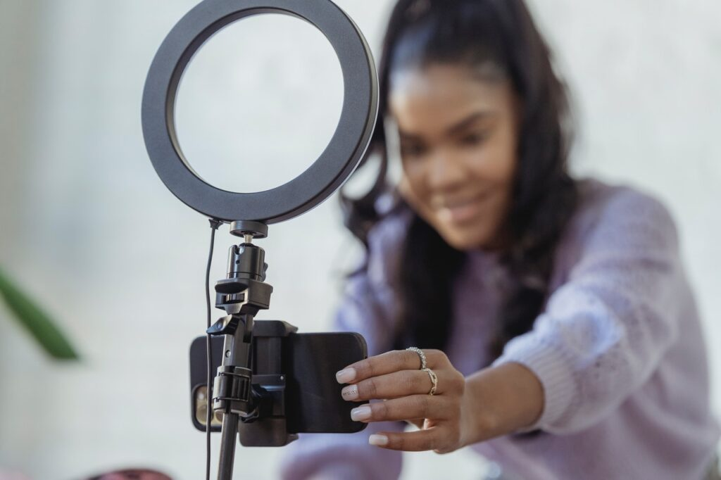 Woman setting up a camera phone on a stand with ring light above it